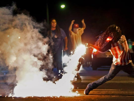 In this Aug. 13, 2014, file photo Edward Crawford Jr., returns a tear gas canister fired by police who were trying to disperse protesters in Ferguson, Mo.