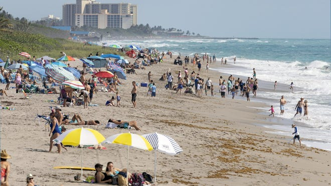 Crowds fill the beach north of the Juno Beach Pier Saturday, May 23, 2020. While it appears the beachgoers are close together because of the compressed perspective of a telephoto lens, people were actually practicing social distancing.