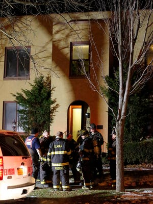 Fire fighters gather outside 351 College Avenue after putting out a kitchen fire Wednesday evening in Elmira.