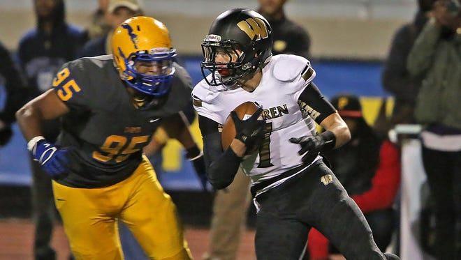 Warren Central quarterback Zach Summeier #7 keeps the ball as Carmel's #95 Rodney Haywood closes in during the Warren Central at Carmel High School football game, Friday, October 9, 2015.  Carmel won 30-20.