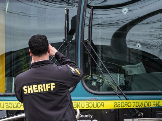 Investigators examine bullet holes in the driver's