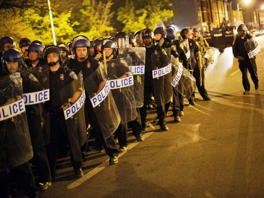 Police in riot gear line up near the scene of Monday's riots ahead of a 10 p.m. curfew Wednesday in Baltimore. The curfew was imposed after unrest in Baltimore over the death of Freddie Gray while in police custody.