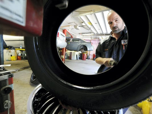 Lonnie Markle, a mechanic with 83 Automotive Center, works to replace a tire rim in the Conewago Township garage on July 16. Last year, the station was one of several hundred that was sanctioned by the Pennsylvania Department of Transportation for inspection violations. PennDOT suspended the station's ability to do emissions testing, but the department allowed it to continue doing other work. Markle was one of several local mechanics who was named in PennDOT documents for local stations that received suspensions or points instead of suspensions in 2014.