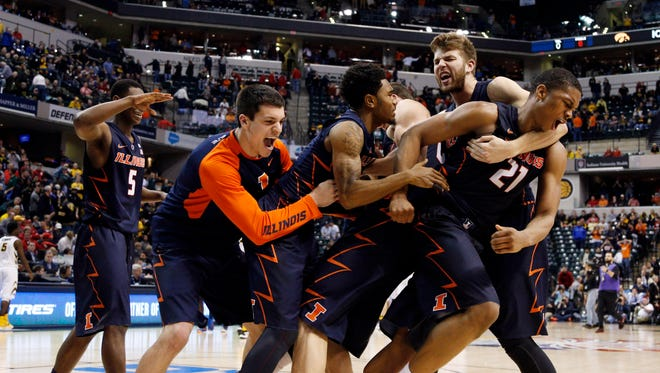 Illinois Fighting Illini guard Malcolm Hill (21) celebrates  with center Maverick Morgan (22) and forward Michael Finke (43) after defeating the Iowa Hawkeyes during the Big Ten Conference tournament at Bankers Life Fieldhouse. Illinois defeats Iowa 68-66.