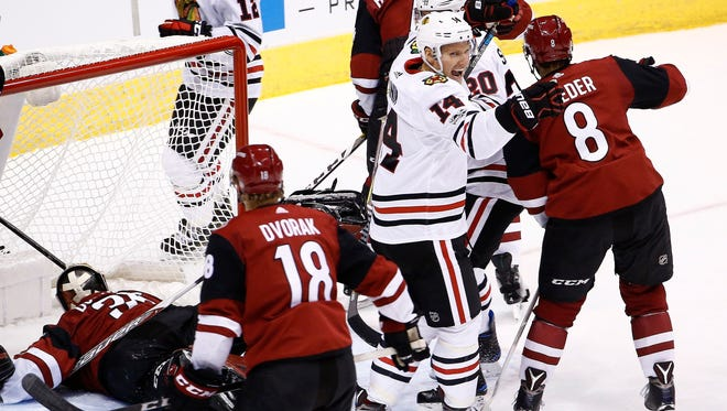 Chicago Blackhawks' Richard Panik (14) celebrates his goal against Arizona Coyotes' Louis Domingue, left, as Coyotes' Christian Dvorak (18) and Tobias Rieder (8) look on during the first period of an NHL hockey game Saturday, Oct. 21, 2017, in Glendale, Ariz.