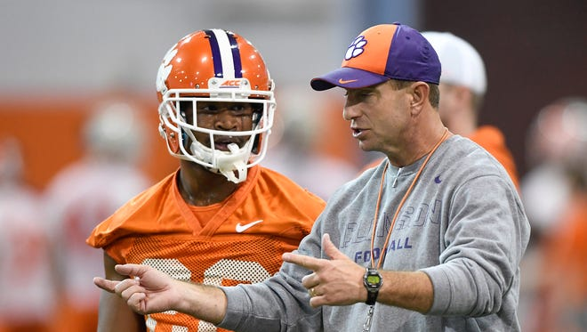 Clemson head coach Dabo Swinney works with running back Adam Choice (26) during the Tigers opening day of spring practice on Wednesday, February 28, 2018.