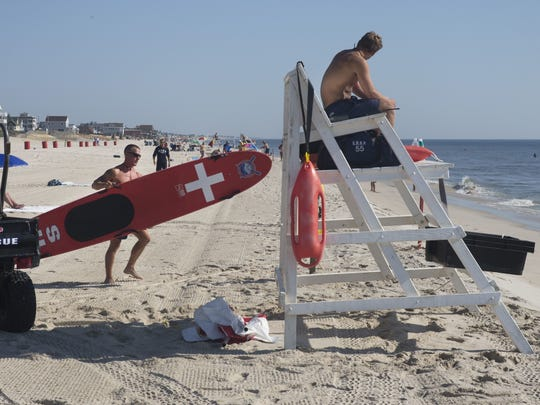 Garret Henshaw, a Seaside Heights guard for five years, deploys lifesaving equipment from storage as he sets up a lifeguard stand at the start of his day last August.