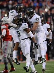 Members of the Spartan defense celebrate Montae Nicholson's