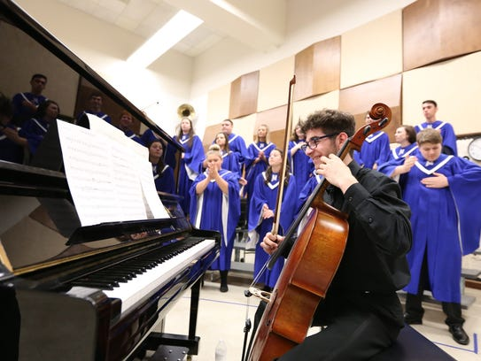 Drew Faatz and the McNary Choir warm up at the OSAA