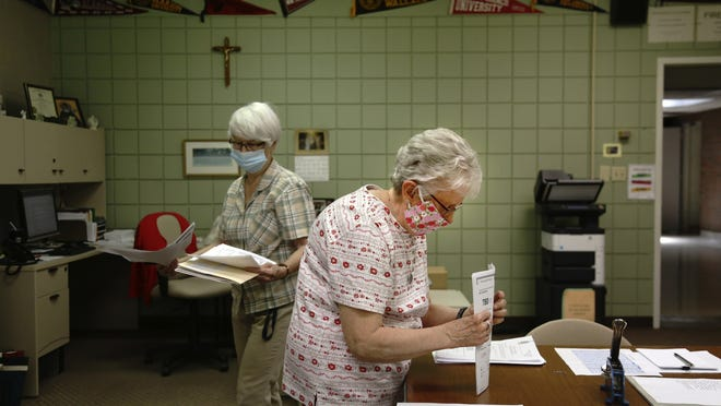Guidance secretary Marge Berckmiller, left, and Sister Bridget Reilly, director of guidance, prepare student transcripts to send to other schools after the  June 8 closure of Quigley Catholic High School in Baden, Pa. The staff learned of the closure May 29 via videoconference.