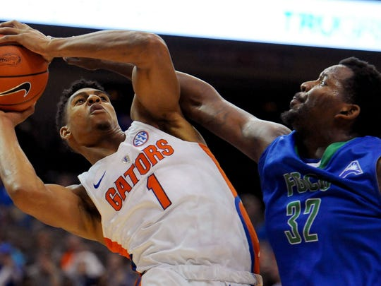Florida forward Devin Robinson fights for a shot against Florida Gulf Coast forward Antravious Simmons during the first half of an NCAA college basketball game, Friday Nov. 11, 2016, in Jacksonville, Fla. (Bob Mack/The Florida Times-Union via AP)