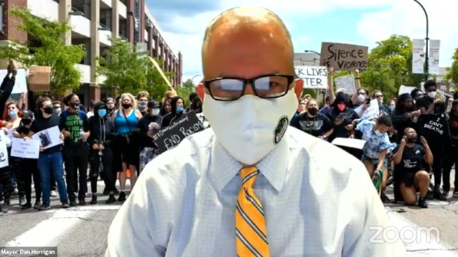 Akron Mayor Dan Horrigan broadcasts his Facebook town hall Monday in front of a photo of demonstrators who protested for police reform in the streets Saturday and Sunday.