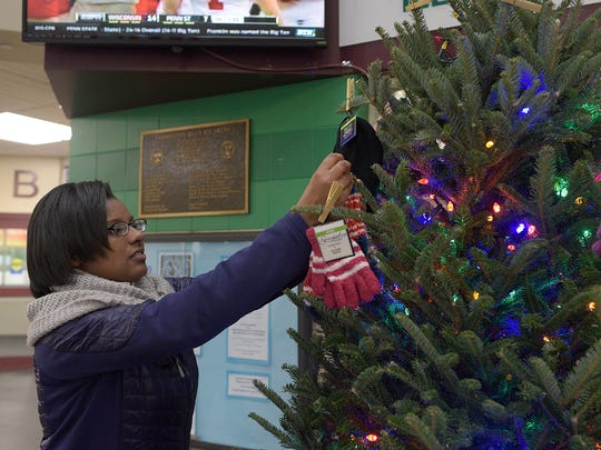 Tamia Austin, 13, hangs a pair of gloves on the Holiday Tree.