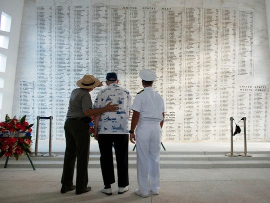 In this June 6, 2013 photo provided by the USS Arizona Memorial Foundation, Lauren Bruner, one of five remaining survivors of the USS Arizona from the Dec. 7, 1941, Japanese attack of Pearl Harbor, is joined by Capt. Jeffry W. James, right, then the commander of Joint Base Pearl Harbor-Hickam, and Daniel Martinez, chief historian for the National Park Service, as they look at the Arizona Memorial's Shrine Wall with names of every man aboard the ship when it was attacked. More than 2,300 servicemen died in the Japanese attack that plunged the United States into World War II. Nearly half of those killed were on the Arizona, most still entombed in the wreckage.