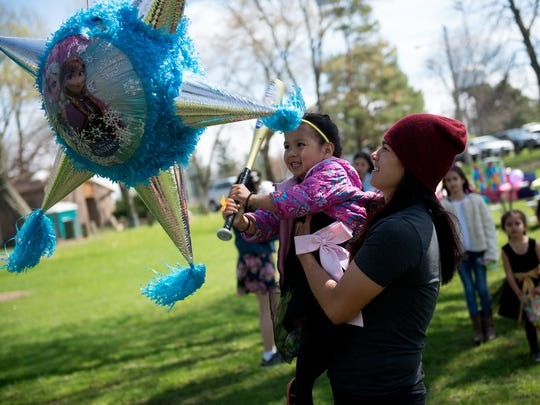 MMA fighter Aurelia Cisneros holds her daughter Lilyana as she tries to break open a pinata on Saturday, April 22, 2017 at Patriarche Park in East Lansing during Lilyana's birthday party. She turned 4.
