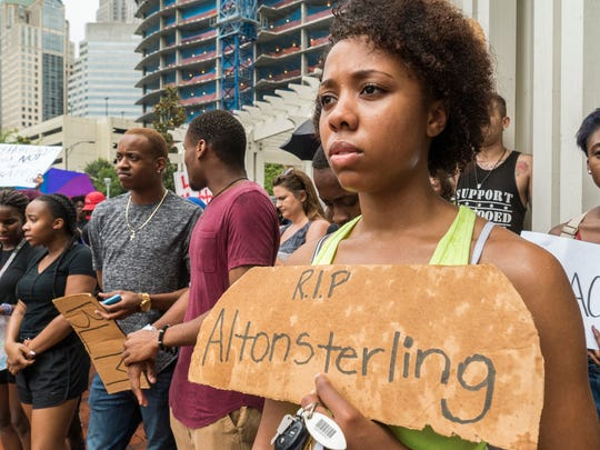 Marcia Bacchus stands quietly with her sign honoring Alton Sterling, killed by police in Baton Rouge, La., during speeches at Romare Bearden Park  People protested the shooting deaths of Philando Castile Wednesday night in Falcon Heights, Minn., after a traffic stop by St. Anthony police, and the death of Alton Sterling, who was shot by Baton Rouge police in Baton Rouge, La., while being detained earlier this week, Thursday, July 7, 2016 in Charlotte, N.C.