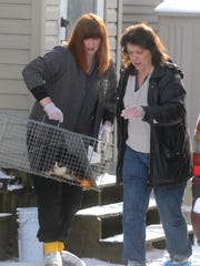 Katie Toschner and Renee Webb, of the Fond du Lac Humane Society carry a cat from a mobile home at W3198 Country Aire Drive in the town of Ashford Tuesday, January 6, 2015.  A total of 42 sick cats were removed  from a feces-filled mobile home, owned by a 79-year-old woman.