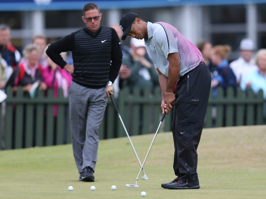 FILE - In this July 16, 2014, file photo, Tiger Woods is watched by coach Sean Foley on the practice green ahead of the British Open Golf championship at the Royal Liverpool golf club in, Hoylake, England. Woods is leaving swing coach Sean Foley after four years and no majors. Woods said on his website Monday, Aug. 25, 2014, he will no longer work with Foley. (AP Photo/Scott Heppell, File)