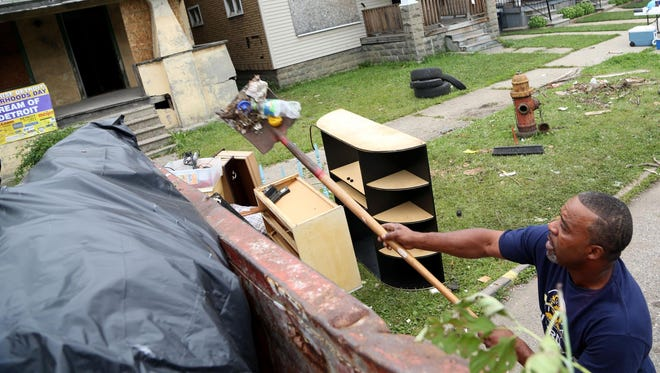 Omar Peterson of Detroit sweeps up small items that were falling out of the dumpster from abandoned homes on Waverly Street in Detroit on August 2, 2014, as part of ARISE Detroit!'s beautification efforts.