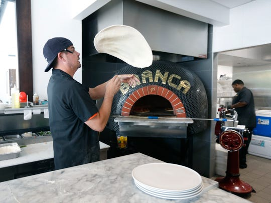 Pizza chef Tom Clarence Parr tosses the dough in the air as he prepares orders during lunch at Branca Midtown restaurant.