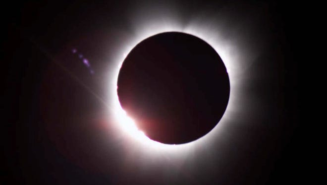 The sun's corona peeks out from behind the moon during the first eclipse of the new millennium in Lusaka, Zambia, Thursday, June 21, 2001. The eclipse lasted three minutes and 14 seconds over Lusaka. Dr. Donald Liebenberg said he extended his view of the eclipse using a tree.