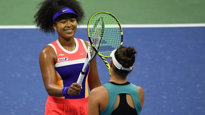 Naomi Osaka touches racquets with Jennifer Brady after their U.S. Open semifinal match on Thursday.