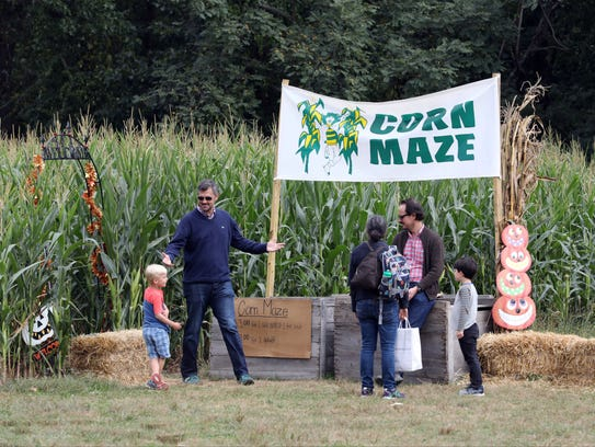 """People mill around the entrance to the """"Corn Maze"""""""