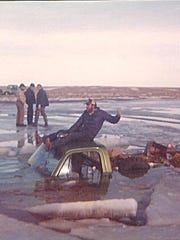 Steve Schindler goofs around on top of his pickup after it fell through the ice on Nelson Reservoir in December 1976.