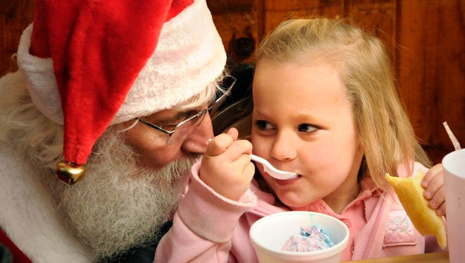 In 2012, Santa talks with a little girl as she eats ice cream and nibbles a bread stick at Charlie's Pizza in Little Falls on Christmas day. It was the second year of the now annual event. Owner Charlie Peterka opened his restaurant and served free pizza to anyone who did not have holiday plans.