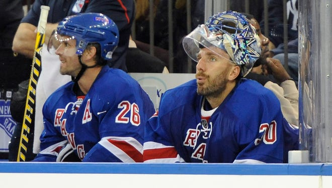 Rangers goalie Henrik Lundqvist, right, sits on the bench next to Martin St. Louis after being taken out of the game after the Toronto Maple Leafs' David Clarkson scored in the second period at Madison Square Garden on Sunday.