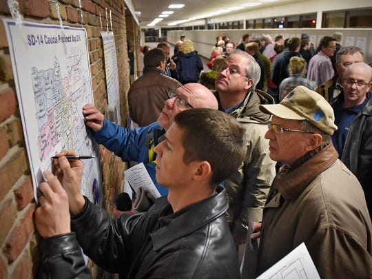 In this 2016 file photo voters look at a map to find their precinct during the Senate District 14 Republican Caucus at Apollo High School in St. Cloud.