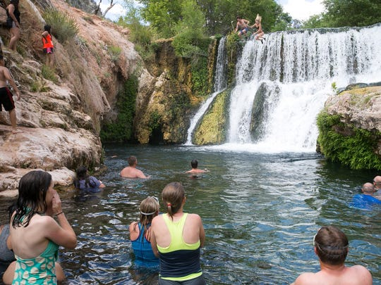 Hikers watch as a couple jump off the old dam at Fossil Springs on Friday, June 12, 2015.