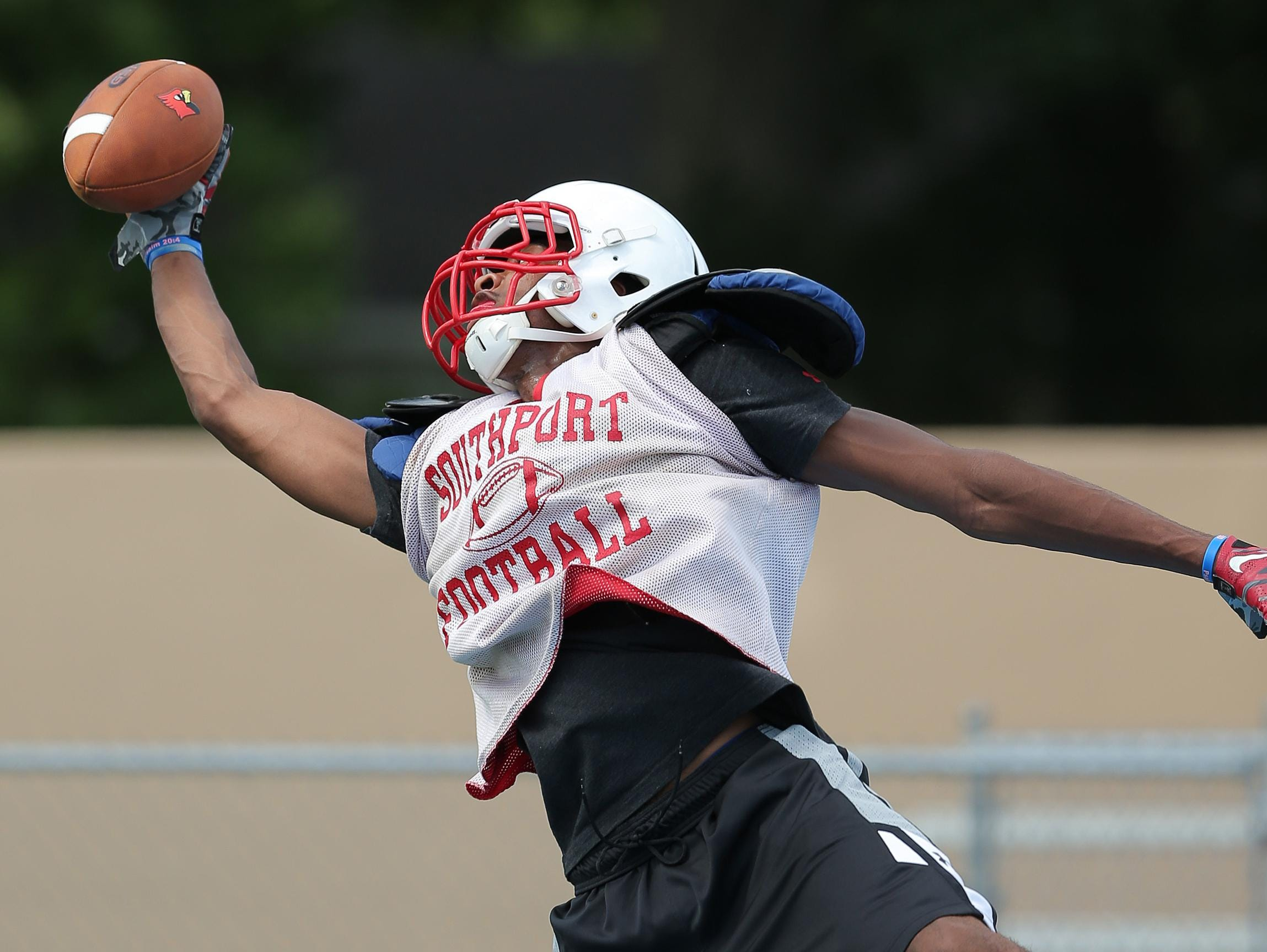 Southport basketball star Paul Scruggs makes a one-handed catch from quarterback Luke Johnston during practice, Aug. 12, 2015. Scruggs is playing football this season as a wide receiver for the first time.