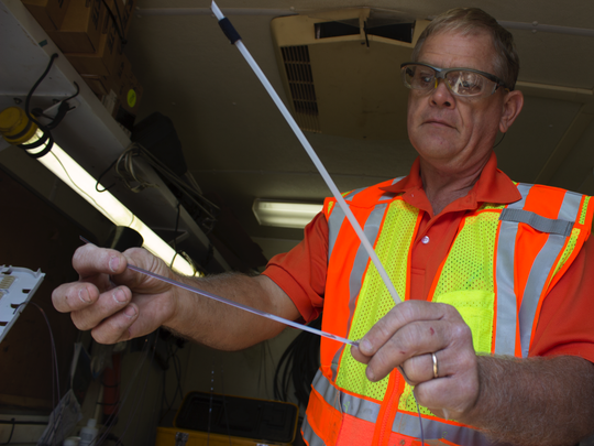 AT&T facility technician Paul Atwood displays a recently spliced fiber which will be wired in an underground fiber optic cable to transmit Internet access in Panola County.