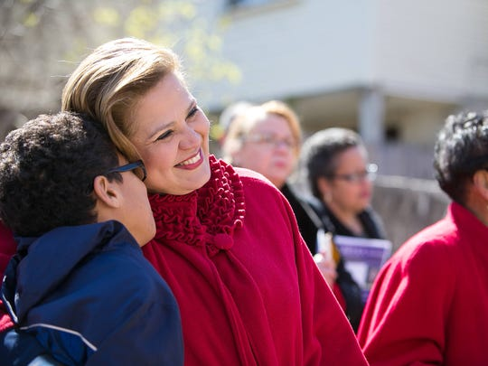 Maria Cabrera hugs her son Vincent, 12, after she announces her candidacy for mayor at a press conference along the 800 block of Windsor Street in Wilmington.