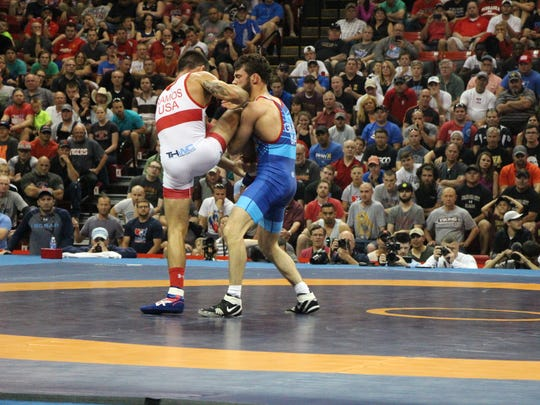 Thomas Gilman (blue singlet) attempts to take down former Iowa teammate Tony Ramos in the championship series of Saturday's Senior World Team Trials at the Devaney Center in Lincoln, Neb.