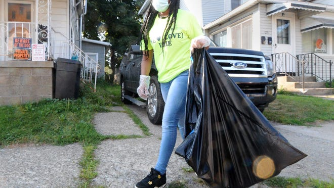 Youth Leadership Institute of Erie member Dijyzariona Lomax, 14, picks up trash in the 700 block of East 22nd Street on Saturday. About 15 members gathered to help beautify the neighborhood.