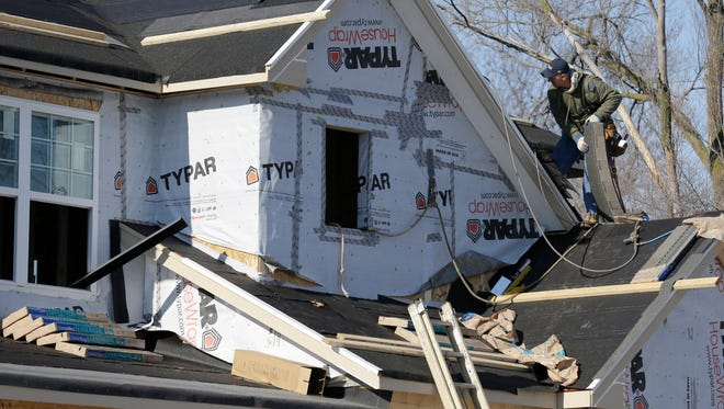 A builder works on the the roof of a new home under construction in Wilmette, Ill.