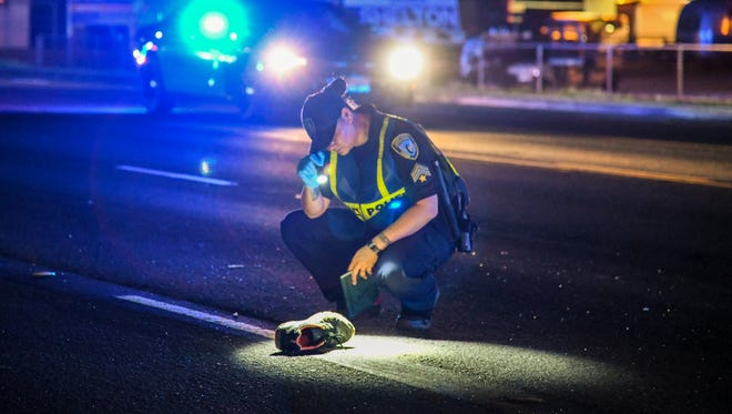 Highway Patrol officer Morgan Reyes gets a close up look of a sneaker lying on Marine Corps Drive as she and other Guam Police Department personnel conduct an investigation of a fatal auto-pedestrian collision in Anigua on Monday, July 16, 2018.