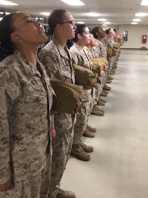 Female Marines stand at attention in the barracks after getting roused at 4 a.m. at Parris Island, S.C., on Feb. 2, 2018.
