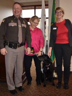 From left, Mason County Sheriff Casey Salisbury and Courthouse Dogs Foundation executive director Celeste Walsen and founder Ellen O'Neill-Stephens with therapy dog Molly laugh at the monthly Mason County Sheriff's Office breakfast, Friday, March 30, at Little Creek Casino Resort in Shelton. Salisbury would like to bring therapy dogs to Mason County's criminal justice system.