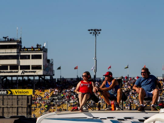 Fans watch the NASCAR XFINITY Series race from the roof of an RV on Saturday, Nov. 14, 2015. Infield camping like this will phase out after the NASCAR and IndyCar races in the spring of 2018.