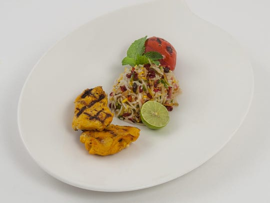 Saffron butter chicken kabob is accompanied by jeweled rice, a Persian mainstay featuring basmati rice studded with colorful dried fruits and nuts.
