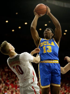 UCLA forward Ike Anigbogu (13) shoots over Arizona forward Lauri Markkanen during the first half of an NCAA college basketball game, Saturday, Feb. 25, 2017, in Tucson, Ariz. (AP Photo/Rick Scuteri)