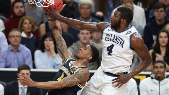 Villanova Wildcats forward Eric Paschall (4) blocks a shot by Michigan Wolverines guard Charles Matthews (1) in the first half in the championship game of the 2018 men's Final Four at Alamodome.