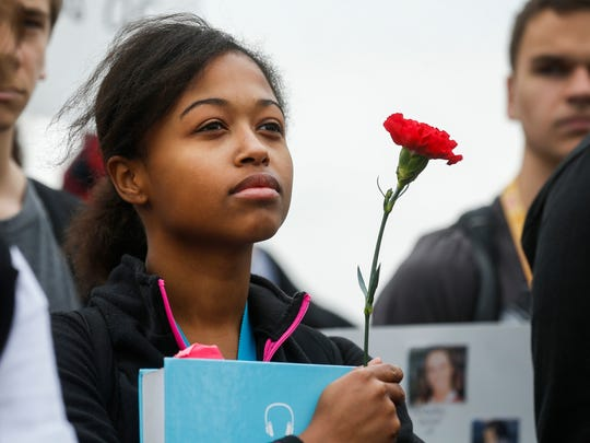 Maria Lloyd, a student at Kickapoo High School, holds a flower as she listens to speakers on Friday, March 23, 2018 on the football field. At least 300 students at Kickapoo High School walked out of class at 10:30 a.m. in response to the fatal school shooting in Parkland, Florida and to raise awareness to gun violence. About 40 students rallied in front of the school to show their support for the 2nd Amendment.