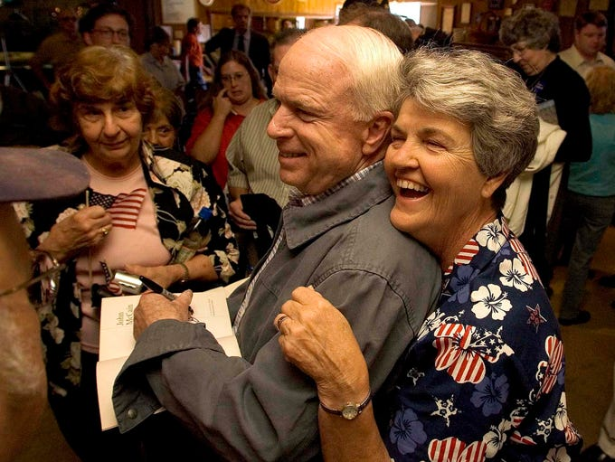 Lucy Kluever (right) sneaks in behind Sen. John McCain