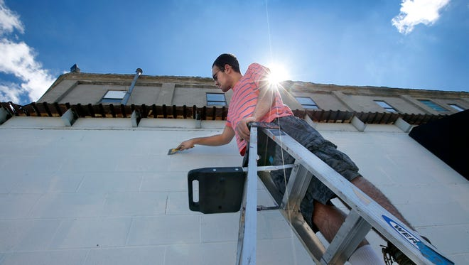 Slade Gonzalez, 19, from Holley, Orleans County, helps others scrape a wall before painting white to prep it for WALL\THERAPY 2018 at the Fedder Building.