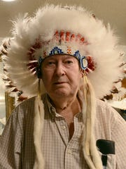 Dave Larson wears an authentic Native American headdress at his wife's Antique Clothing Museum in Lemmon Valley.