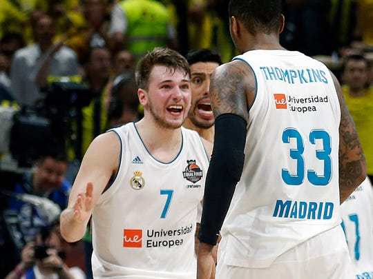 FILE - In this May 20, 2018, file photo, Real Madrid's Luka Doncic (7) reacts with teammate Trey Thompkins after winning their Final Four Euroleague final basketball match against Fenerbahce, in Belgrade, Serbia. The Slovenian guard heads the list of international players expected to be selected in the NBA draft. (AP Photo/Darko Vojinovic, File)